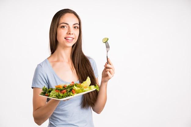 Mujer sosteniendo una ensalada y mirando a cámara