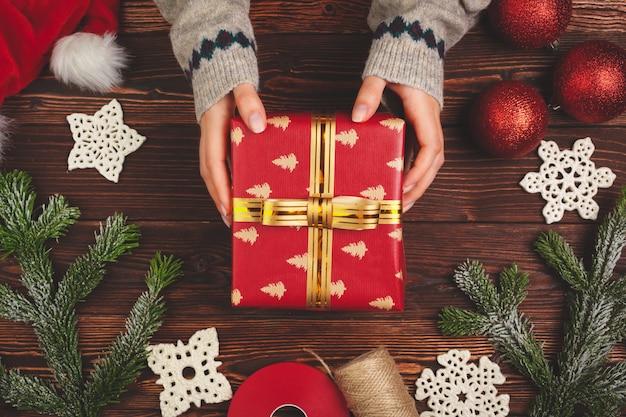 Mujer sosteniendo envuelto regalo de navidad en sus manos, vista desde arriba