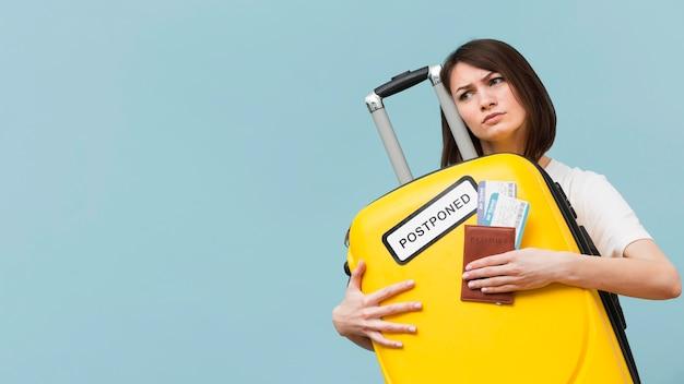 Mujer sosteniendo un equipaje amarillo con un cartel pospuesto con espacio de copia