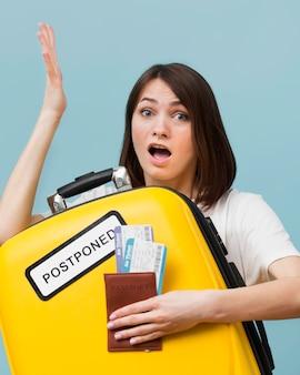 Mujer sosteniendo un equipaje amarillo con un cartel pospuesto mientras sostiene boletos de avión
