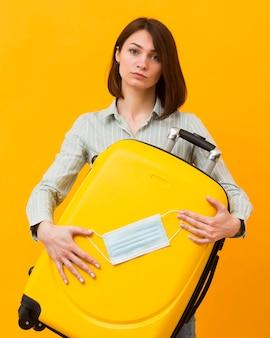 Mujer sosteniendo un equipaje amarillo y una máscara médica