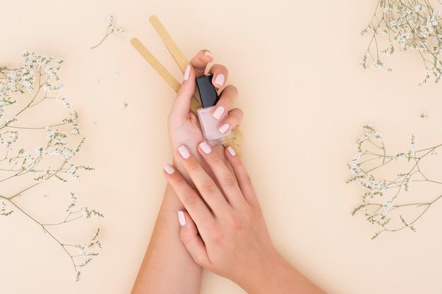 Mujer sosteniendo un esmalte de uñas