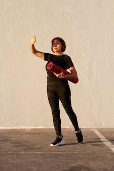 Mujer sosteniendo una estera de fitness y cubre sus ojos del sol