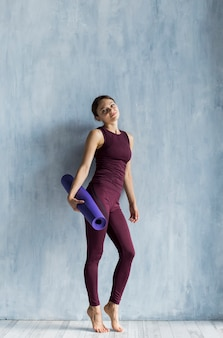 Mujer sosteniendo una estera de yoga en la mano