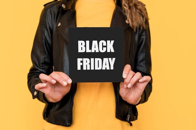 Mujer sosteniendo etiqueta de viernes negro