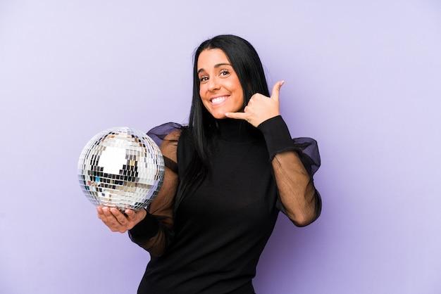 Mujer sosteniendo una fiesta de pelota aislada en púrpura mostrando un gesto de llamada de teléfono móvil con los dedos.