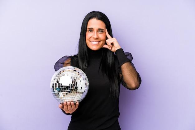 Mujer sosteniendo una fiesta de pelota en la pared púrpura que señala el templo con el dedo
