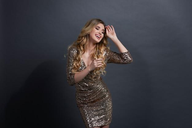 Mujer sosteniendo flauta de champán y bailando