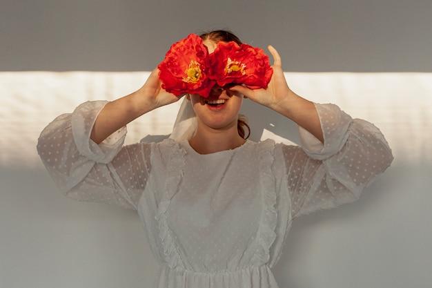Mujer sosteniendo flores sobre los ojos