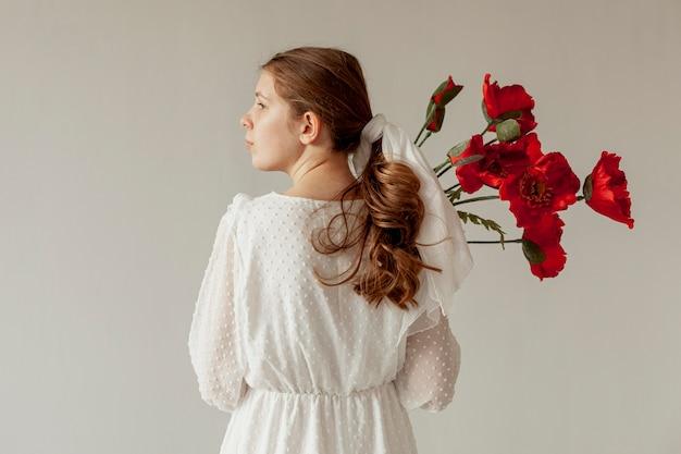 Mujer sosteniendo flores vista posterior