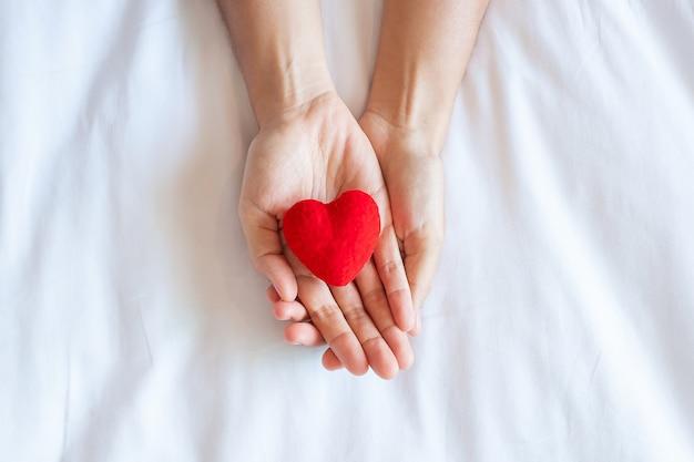 Mujer sosteniendo en forma de corazón rojo sobre fondo blanco de cerca