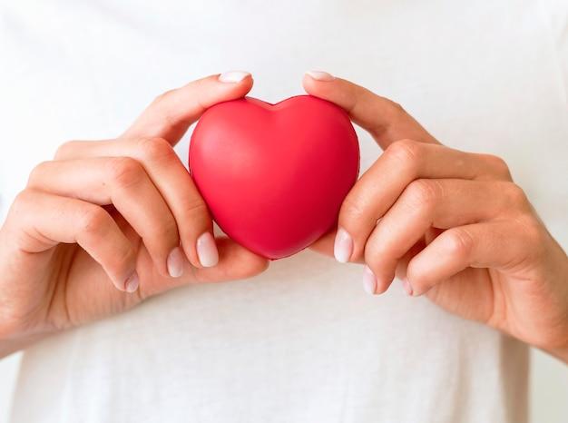 Mujer sosteniendo en forma de corazón