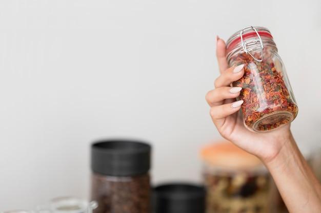 Mujer sosteniendo un frasco con especias con espacio de copia