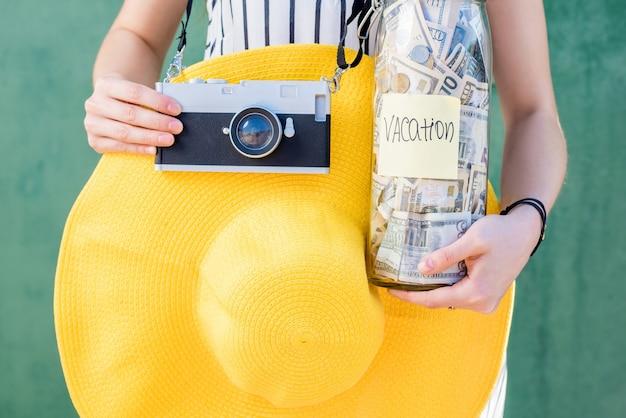 Mujer sosteniendo un frasco lleno de ahorros de dinero para las vacaciones de verano con sombrero amarillo y cámara de fotos sobre fondo verde