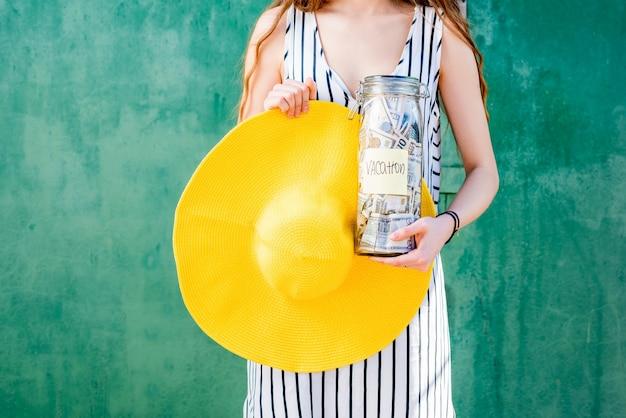 Mujer sosteniendo un frasco lleno de ahorros de dinero para las vacaciones de verano con sombrero amarillo sobre fondo verde