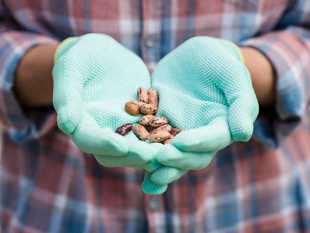 Mujer sosteniendo frijoles en sus manos
