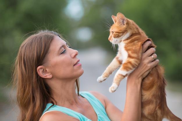 Mujer sosteniendo un gato en sus brazos y abrazándose al aire libre en el parque