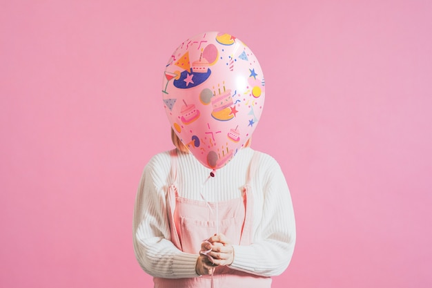 Mujer sosteniendo globo festivo sobre fondo rosa liso