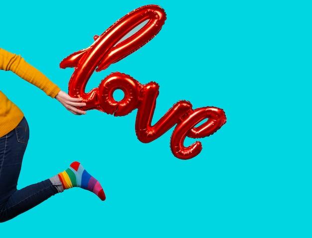 Mujer sosteniendo globo con la palabra amor y calcetines arcoiris