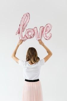 Mujer sosteniendo un globo de papel de amor