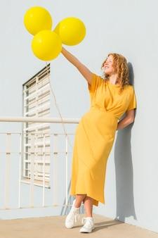 Mujer sosteniendo globos amarillos