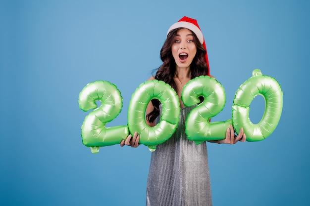 Mujer sosteniendo globos de año nuevo 2020 con sombrero y vestido de navidad
