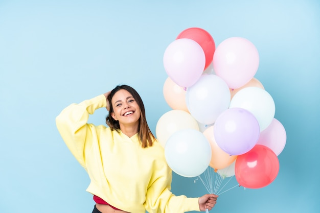 Mujer sosteniendo globos en una fiesta sobre pared azul aislado riendo