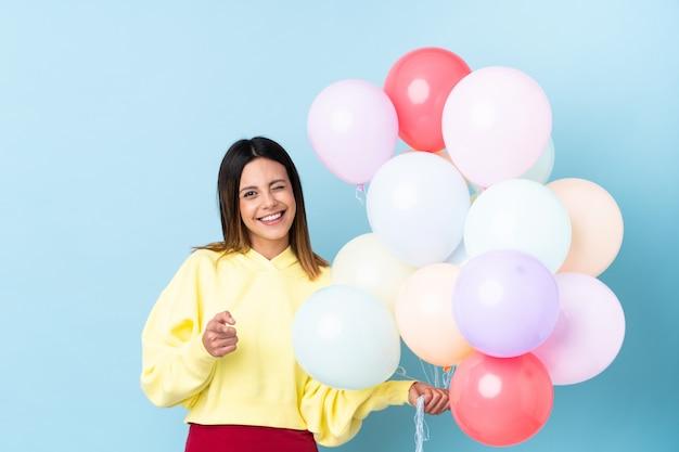 Mujer sosteniendo globos en una fiesta te señala con el dedo
