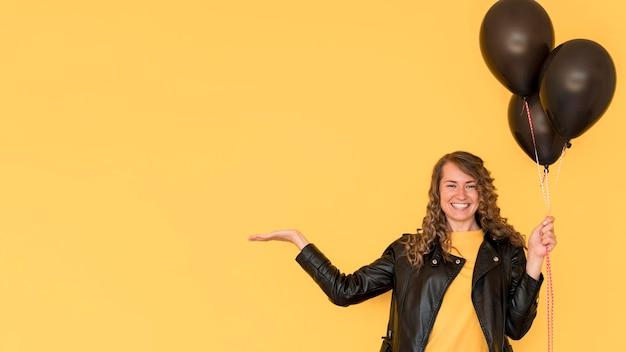 Mujer sosteniendo globos negros copia espacio