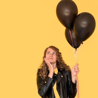 Mujer sosteniendo globos negros