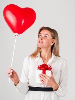 Mujer sosteniendo globos y regalos para san valentín