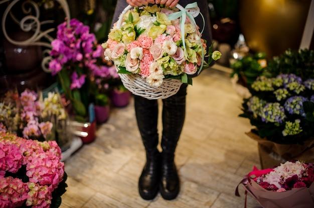 Mujer sosteniendo una gran cesta de mimbre con flores.