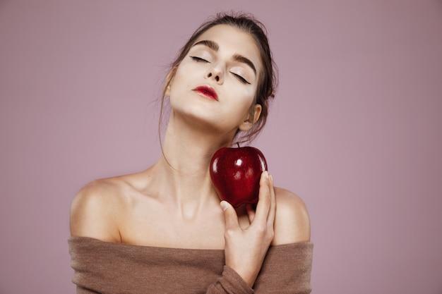Mujer sosteniendo gran manzana roja en rosa