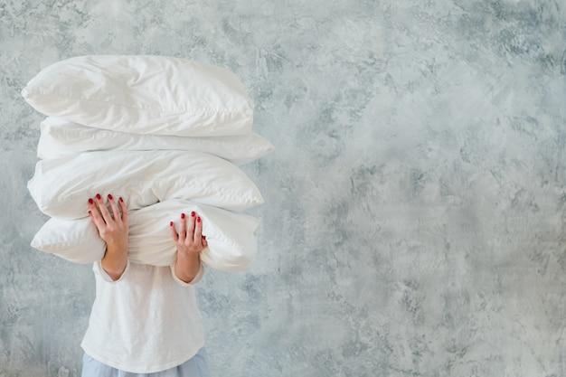 Mujer sosteniendo gran montón de almohadas blancas suaves y acogedoras en la pared gris. concepto de ropa de cama y dormir