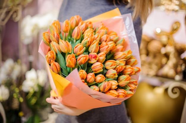 Mujer sosteniendo un gran ramo brillante de tulipanes naranjas