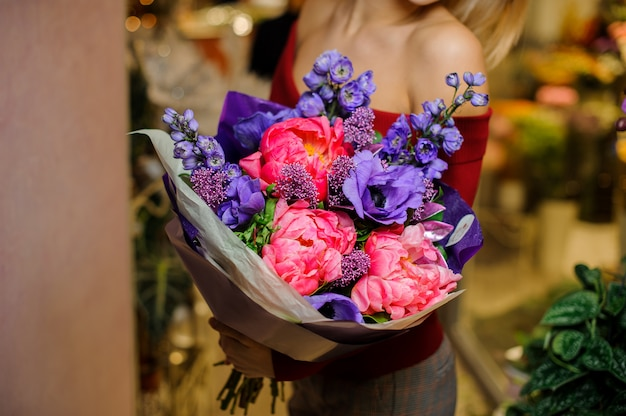 Mujer sosteniendo un gran ramo de flores de color púrpura y rosa para el día de san valentín