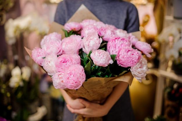 Mujer sosteniendo un gran ramo de peonías rosas