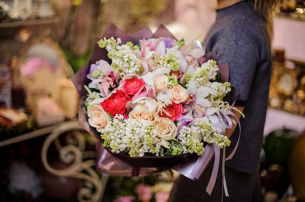 Mujer sosteniendo un gran ramo de rosas y otras flores