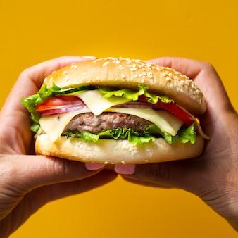 Mujer sosteniendo una hamburguesa con ambas manos
