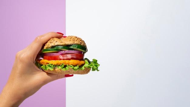 Mujer sosteniendo una hamburguesa vegetal en su mano