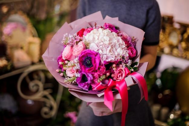 Mujer sosteniendo un hermoso ramo de flores rosas diferentes