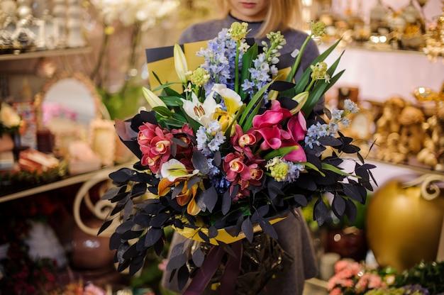 Mujer sosteniendo un hermoso ramo de orquídeas, lirios y hermosas hojas.