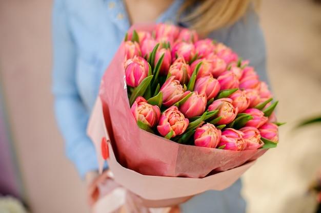 Mujer sosteniendo un hermoso y tierno ramo de tulipanes rosados