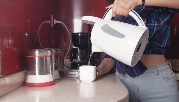 Mujer sosteniendo hervidor y vertiendo agua en la taza. preparando bebida caliente