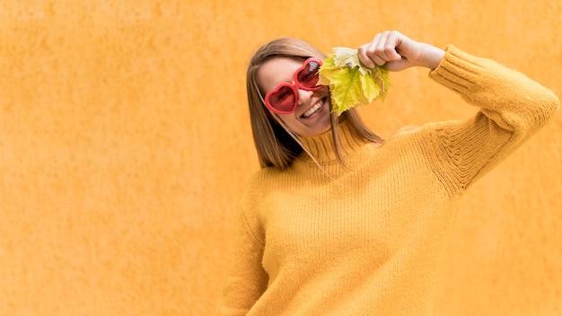 Mujer sosteniendo una hoja de otoño