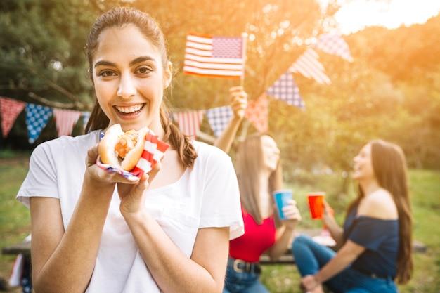 Mujer sosteniendo hot-dog en manos
