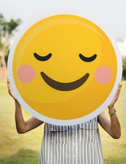 Mujer sosteniendo un icono de cara sonriente