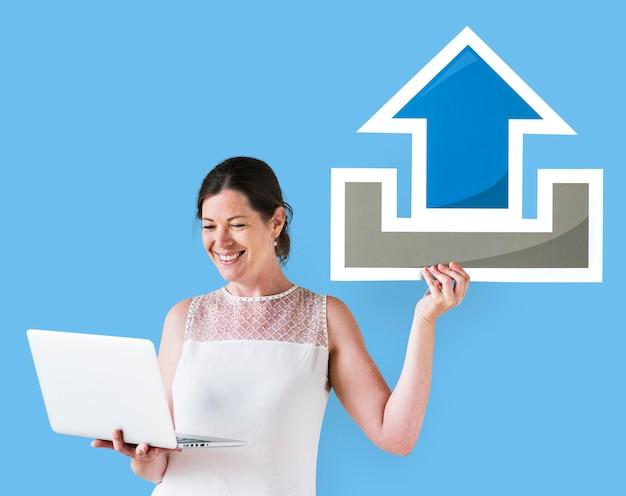 Mujer sosteniendo un icono de carga y una computadora portátil