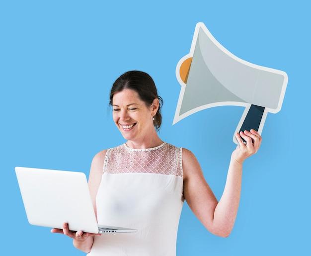 Mujer sosteniendo un ícono de megáfono y usando una laptop
