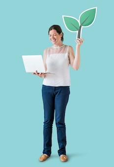 Mujer sosteniendo un icono de planta y usando una laptop